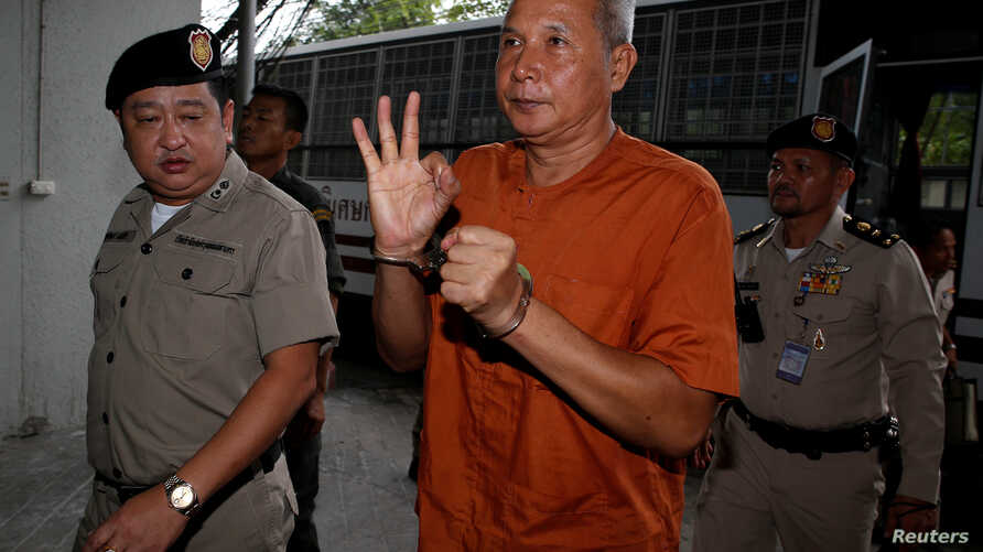 Thanat Thanawatcharanon, also known by his stage name Tom Dundee, a Thai actor, singer and political activist, who was accused of insulting Thailand's king in public speech, gestures as he arrives at the criminal court in Bangkok, Thailand, June 1, 2