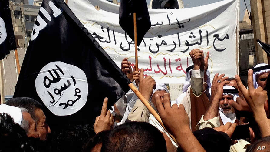 FILE - Demonstrators chant pro-al-Qaida-inspired Islamic State of Iraq and the Levant (ISIL) statements as they wave al-Qaida flags in front of the provincial government headquarters in Mosul, Iraq.