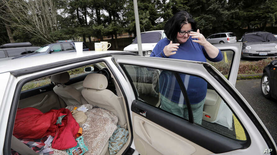 Lisa Davis shows how she has her car set up to live in the church parking lot she shares with two-dozen or so other vehicles and their occupants, homeless single women, in Kirkland, Wash., March 5, 2018.