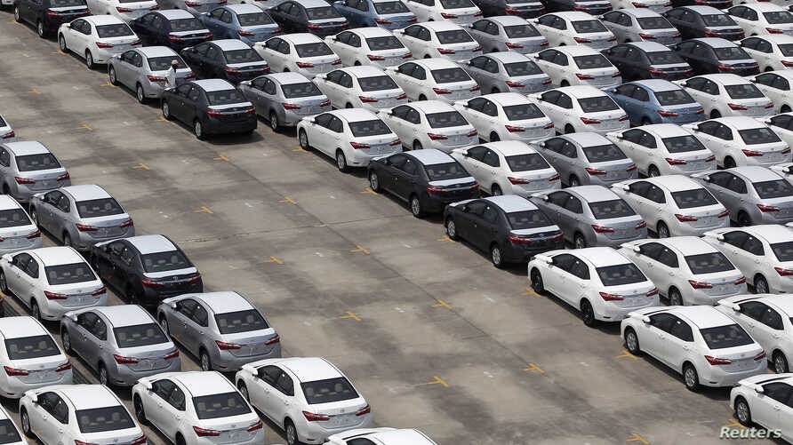 A man walks among cars which are ready for export at the port of Taipei, northern Taiwan, April 16, 2014.