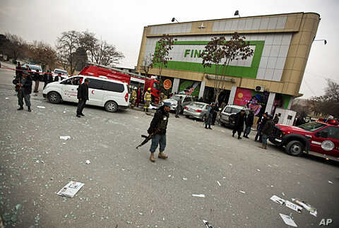 Afghan policeman keeps watch after a suicide bomb attack at Finest supermarket in Kabul, January 28, 2011