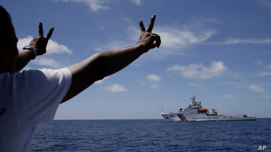 FILE - Philippine crewmen gestures towards a Chinese Coast Guard ship as they block them from entering Second Thomas Shoal in the South China Sea, March 29, 2014.