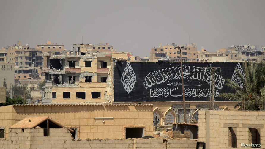 FILE - A banner belonging to Islamic States fighters is seen during a battle with member of the Syrian Democratic Forces in Raqqa, Syria, Aug. 16, 2017.