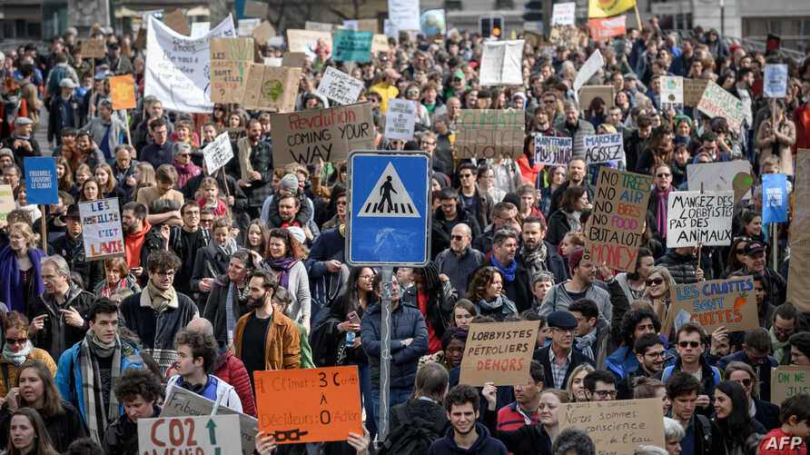 Demonstrators hold placards during a protest against climate change in Lausanne, Switzerland, April 6, 2019.