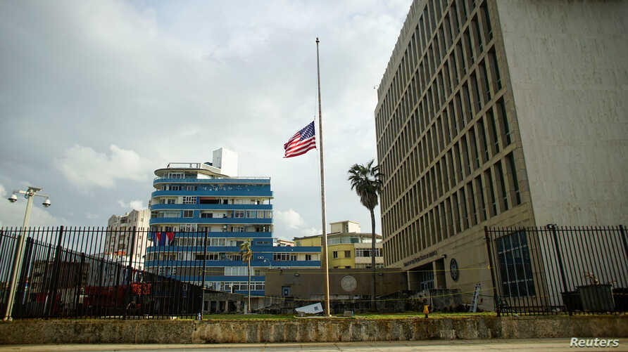 The U.S. flag is lowered to half mast in front of a damaged fence of the U.S. embassy after Hurricane Irma caused flooding and a blackout, in Havana, Cuba Sept. 11, 2017.