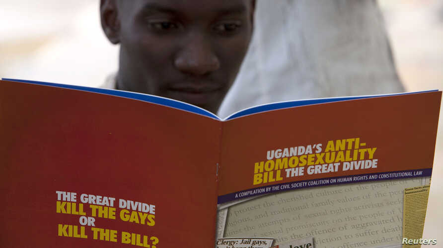 FILE - A man reads a publication by a civil society coalition on human rights and constitutional law in Kampala.