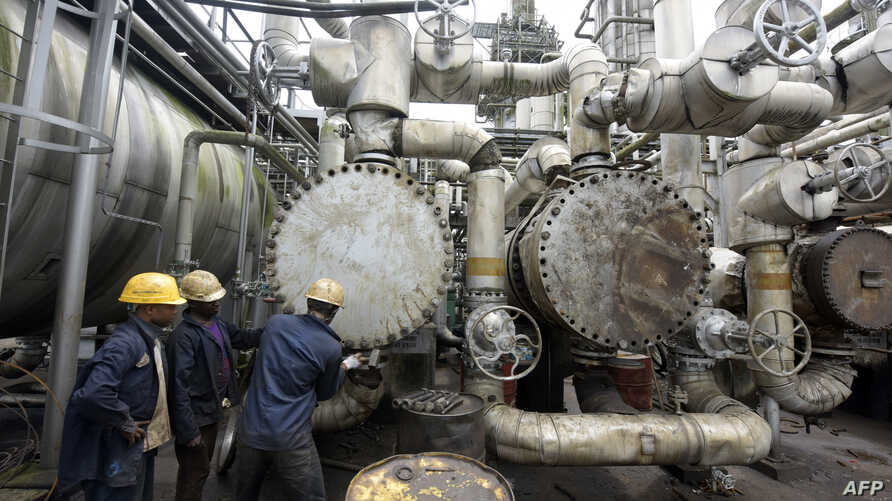 FILE - Workers try to tie a pipe at an oil refinery in Port Harcourt, Rivers State, Nigeria, Sept. 16, 2015.