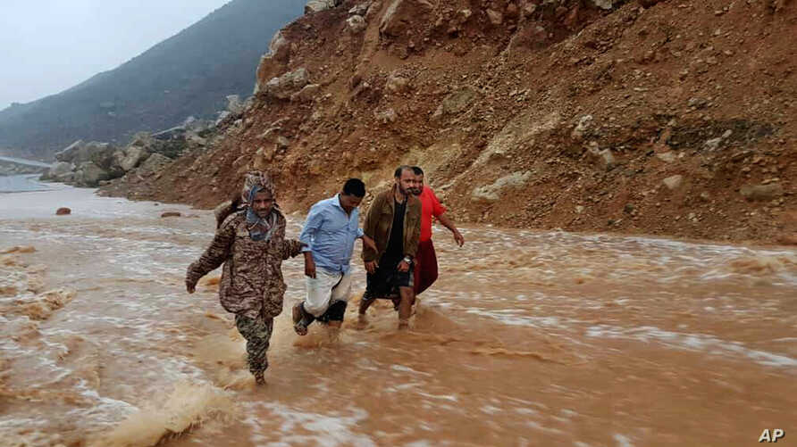 Men walk on a road flooded after heavy rain and strong winds caused damage in Hadibu as Cyclone Mekunu pounded the Yemeni island of Socotra, May 24, 2018. At least 17 people were reported missing and presumed dead. The powerful storm remained on path