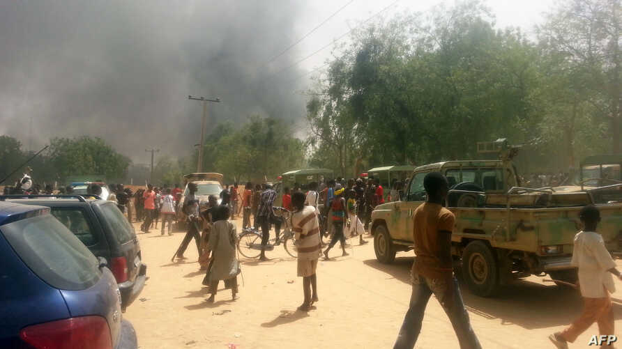 People look at smoke rising after suspected Boko Haram Islamists attack a military base in the northeast Nigerian city of Maiduguri. Boko Haram has claimed responsibility for an attack on a key military barracks in the northeastern city of Maiduguri,