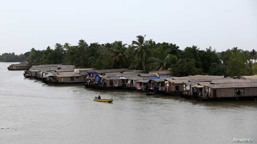 A motorboat moves past a row of empty houseboats in a tributary of the Pamba river following floods in Alappuzha district in the southern state of Kerala, India, Aug. 24, 2018.