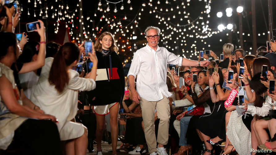 FILE - Model Gigi Hadid and designer Tommy Hilfiger acknowledge attendees after presenting Hilfiger's Spring/Summer 2017 collection at New York Fashion Week in Manhattan, New York.