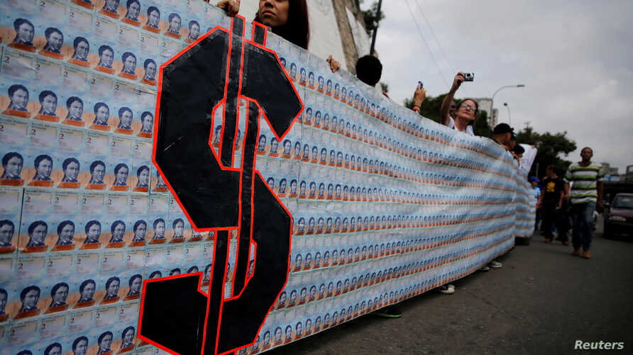 FILE - Demonstrators hold a banner made from three thousand two-bolivar-bills, that is equivalent approximately to $1 according to the black market exchange rate, in Caracas, Venezuela, June 10, 2017.