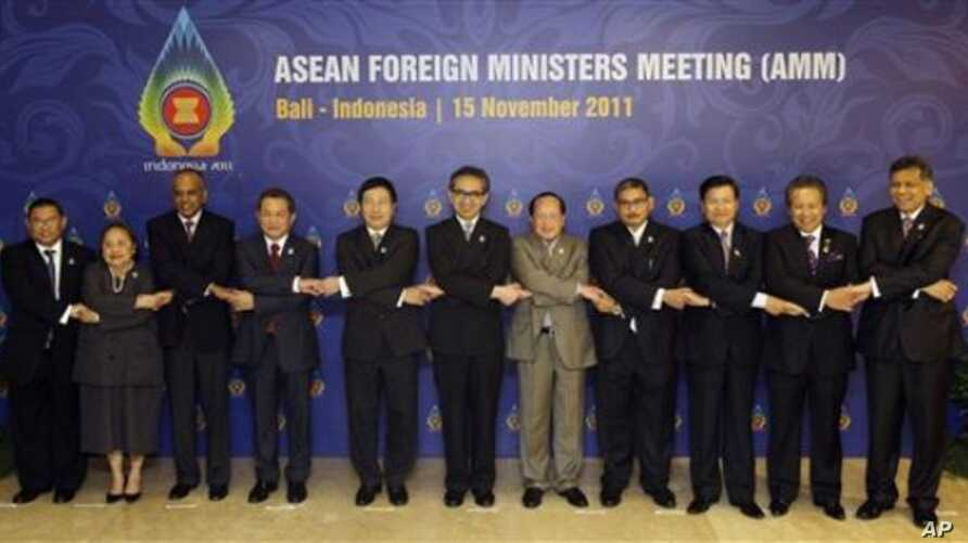 ASEAN foreign ministers and their representatives hold hands during a group photo session of the ASEAN Foreign Ministers Meeting at Bali, Indonesia, November 15, 2011.