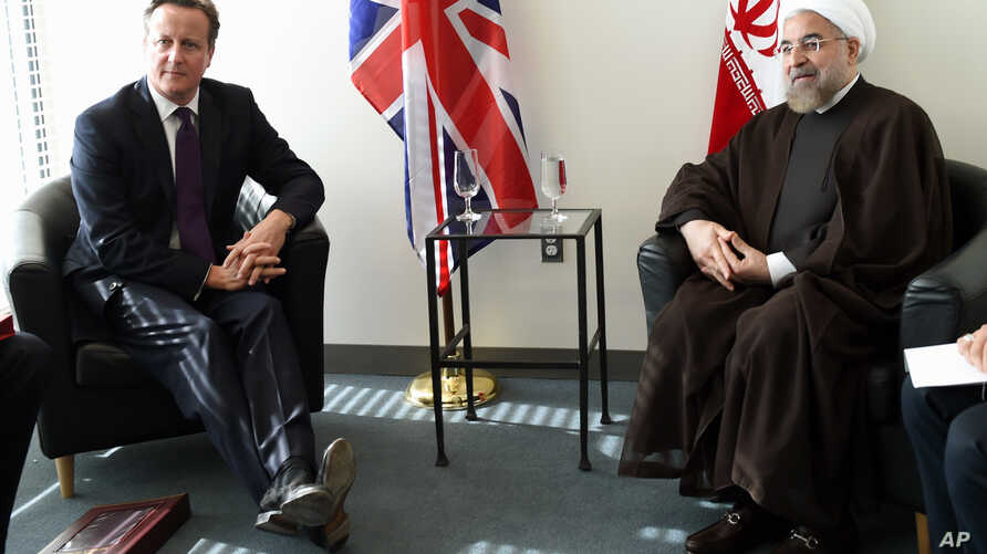 British Prime Minister David Cameron meets with Iranian President Hassan Rouhani at the UN during the 69th Session of the UN General Assembly, Wednesday, Sept. 24, 2014.  (AP Photo/Timothy A. Clary, Pool)