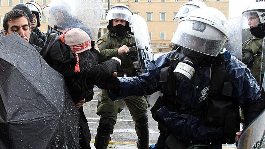 Riot police scuffle with a female protester as they try to open the avenue outside the Greek Parliament during a heavy rain in Athens, February 7, 2012.