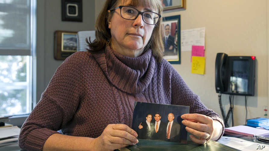 FILE - In this Feb. 11, 2019 photo, Carina Black sits in her office in Reno, Nev., holding an April 6, 1998 photo of herself with Nobel Peace Prize winner and former Costa Rican President Oscar Arias, center, and Richard Siegel, a former University o