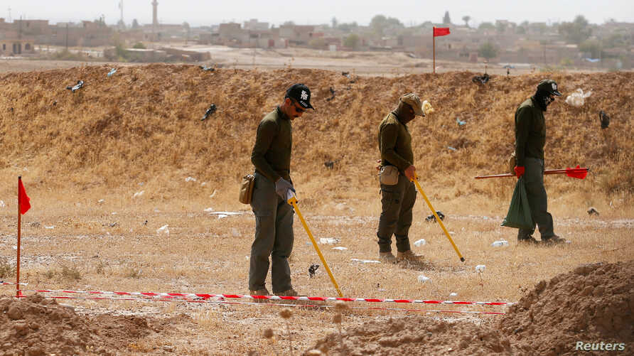 FILE - Mine clearers search for mines and explosive devices at Hammam al-Alil city, south of Mosul, Iraq, July 29, 2017.
