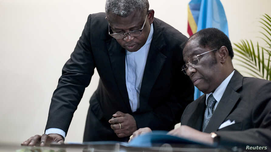 FILE - Congolese Justice Minister Alexis Thambwe Mwamba, right, is assisted by Abbot Donatiuen N'shole, CENCO secretary general, as he signs the accord between the opposition and the government of President Joseph Kabila at CENCO headquarters in Kins