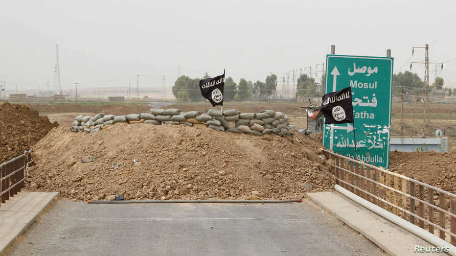 Islamic State flags flutter on the Mullah Abdullah bridge in southern Kirkuk September 29, 2014. Members of the Kurdish security forces and the Islamic State are holding fort behind sandbags on different ends of the bridge. REUTERS/Ako Rasheed (IRAQ