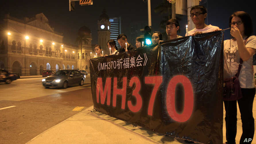 People hold a banner and candles during a candlelight vigil for passengers aboard a missing Malaysia Airlines plane in Kuala Lumpur, Malaysia, Monday, March 10, 2014. The search operation for the missing Malaysia Airlines Flight MH370 which has invol