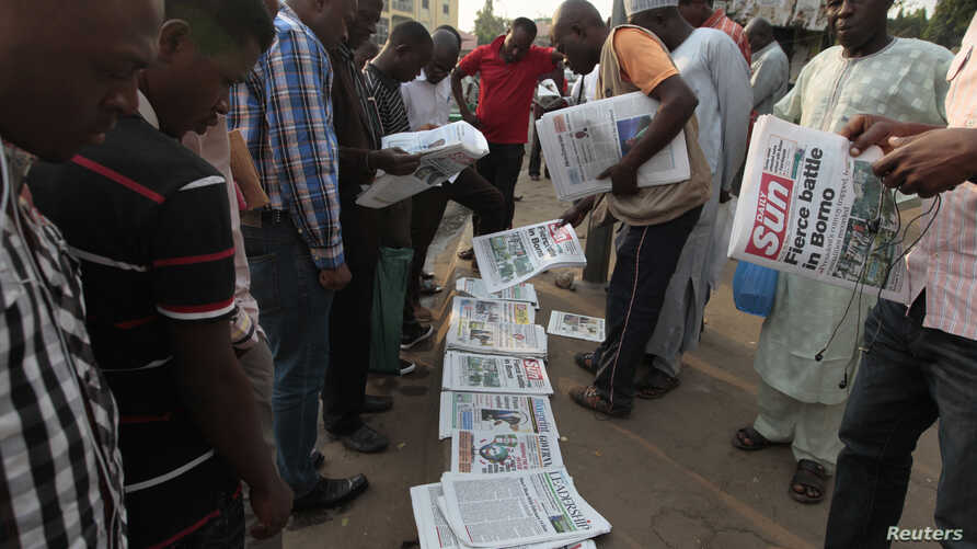 People gather to browse through newspapers at a news stand in Abuja, Nigeria, Jan. 26, 2015.