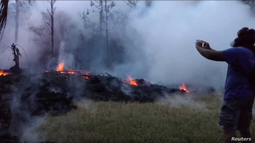 A man wearing a gas mask takes pictures of a lava fissure in Leilani Estates, Hawaii, May 9, 2018, in this still image taken from a social media video.