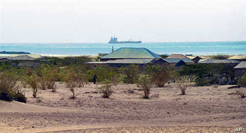 A lone figure makes its way past the bushes in the outskirts of the central Somali coastal town of Hobyo as the outline of a hijacked ship is seen anchored off the coast (File)