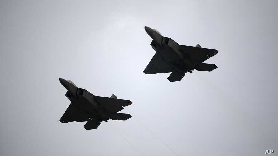 FILE - Two U.S. Air Force F-22 fighter jets perform a flyover during the playing of the national anthem before a NASCAR Cup Series auto race at Daytona International Speedway, July 7, 2018, in Daytona Beach, Florida.