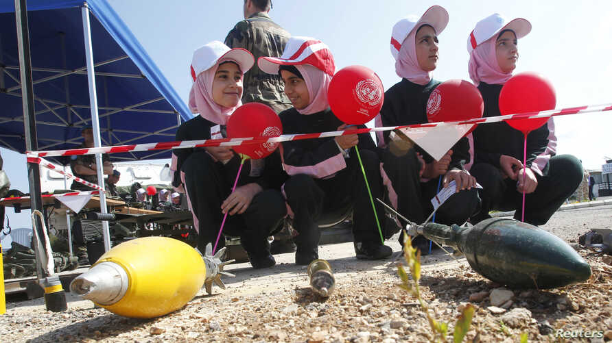 FILE - Schoolchildren attend an awareness campaign teaching them to identify mines and unexploded cluster bombs at the United Nations Interim Force in Lebanon (UNIFIL) headquarters in the town of Naqoura in southern Lebanon, April 4, 2014.