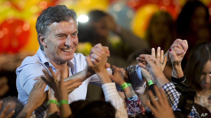Outgoing Buenos Aires Mayor Mauricio Macri holds hands with followers after a mayoral runoff election — won by conservative candidate Horacio Rodriguez Larreta — in Buenos Aires, Argentina, July 19, 2015.