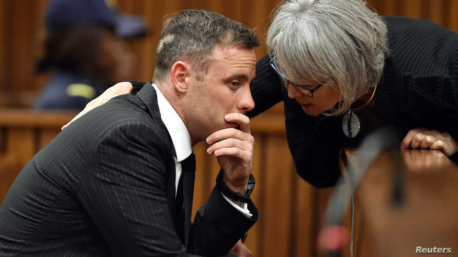 Former Paralympian Oscar Pistorius is comforted by an unidentified woman before his sentencing for the murder of Reeva Steenkamp at the Pretoria High Court, South Africa, June 13, 2016.