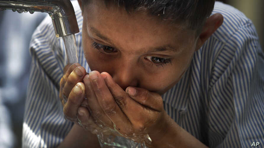 A boy drinks water from a newly set up water filtration tower in his school provided by Planet Water foundation, a non-governmental organization based in U.S. in Nai Basti Village, near New Delhi, India, March 22, 2017.