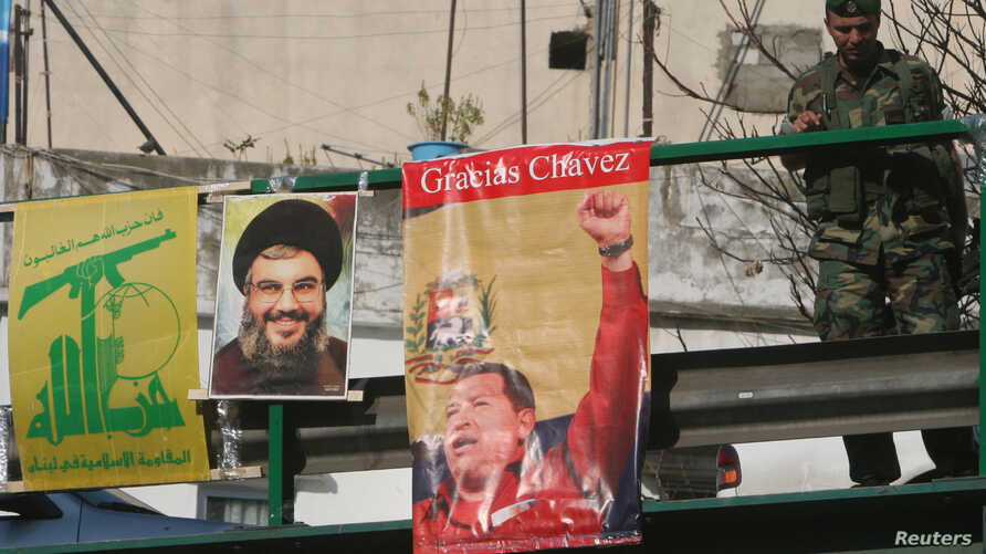 FILE - A Lebanese soldier stands beside posters of Hezbollah leader Sayyed Hassan Nasrallah and Venezuela's President Hugo Chavez on a bridge in Beirut, Dec. 1, 2006.