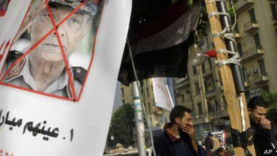 Protesters walk next to a poster against Egypt's military ruler, Field Marshal Mohamed Hussein Tantawi, the head of the Supreme Council of the Armed Forces, at Tahrir Square, the focal point of Egyptian uprising, in Cairo, Egypt, November  27, 2011.