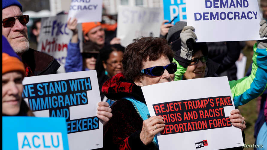 People hold signs during a demonstration against U.S. President Donald Trump on President's day near the White House in Washington, Feb. 18, 2019.