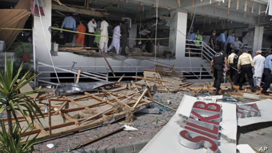 Pakistani security officials examine the site of a suicide bombing in Islamabad, Pakistan. A suicide bomber blew himself up at a busy market in the Pakistani capital, killing at least one person in the first bombing in Islamabad in over a year and a