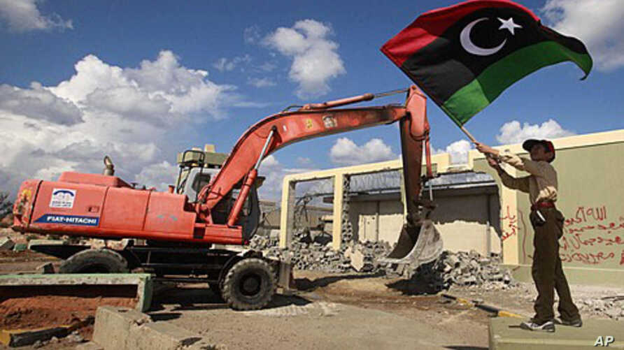 A boy waves a Kingdom of Libya flag as a bulldozer demolishes walls of the residence of Moammar Gadhafi at the Bab al-Aziziyah complex in Tripoli, October 16, 2011.