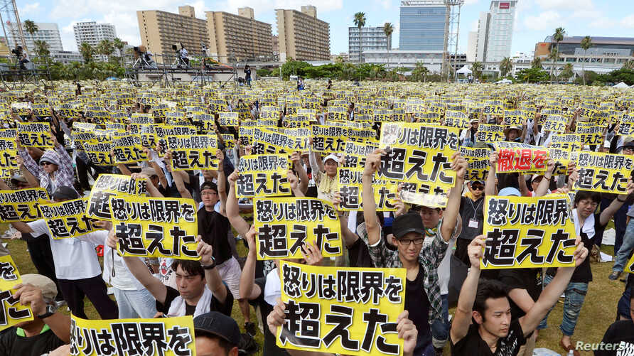 "Protesters raise placards reading ""Anger was over the limit"" during a rally against the U.S. military presence on the island and a series of crimes and other incidents involving U.S. soldiers and base workers, at a park in the prefectural capital Nah"