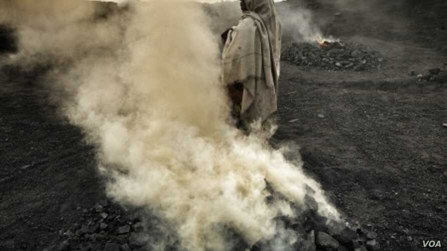 A woman tends fires of burning coal at a village outside Djaria, India. Credit Larry C. Price