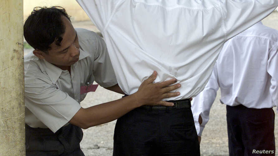 A Cambodian school security official searches a student for exam 'cheat sheets' at the gates of a school in Phnom Penh, Aug. 7, 2003.
