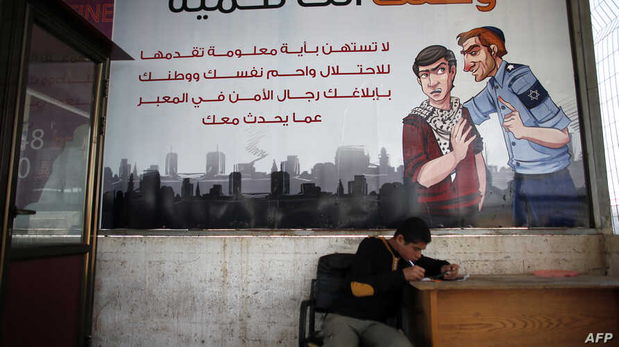 A Palestinian boy sits under a poster hung by Hamas authorities, on the Gaza side of the border crossing with Israel's Erez crossing, in Beit Hanun in the north of the Gaza Strip, May 12, 2015.