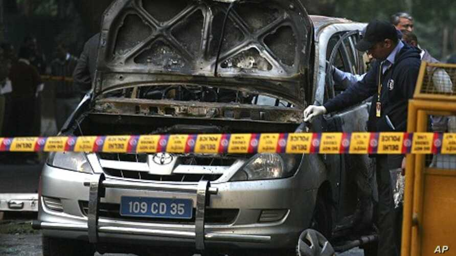 Police and forensic officials examine a damaged Israeli embassy car after an explosion in New Delhi February 13, 2012.
