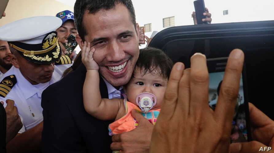 Venezuelan opposition leader and self-proclaimed acting president Juan Guaido (C) poses for a picture with a baby before leaving his hotel in Salinas, Ecuador, March 3, 2019.
