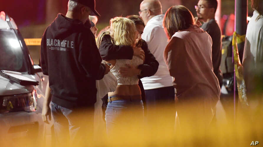People comfort each other as they stand near the scene, Nov. 8, 2018, in Thousand Oaks, Calif. where a gunman opened fire Wednesday inside a country dance bar crowded with hundreds of people.
