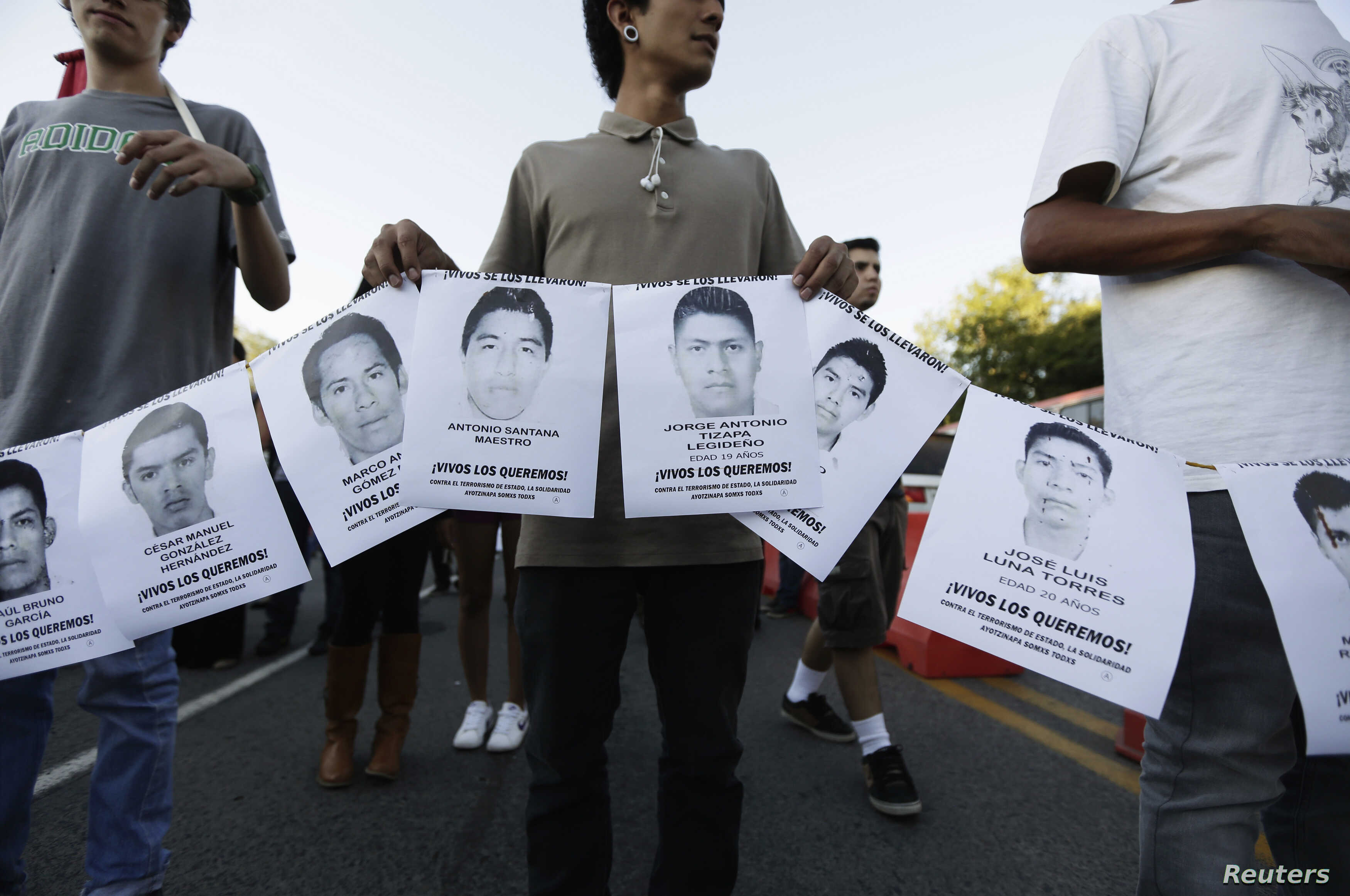 People hold photographs of missing students during a march in their support in Guadalajara Oct. 8, 2014.