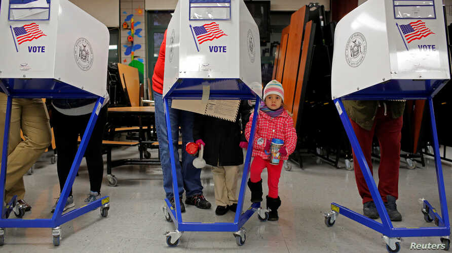 Myla Gibson, 3, waits as her father Ken Gibson fills out a ballot for the U.S presidential election at the James Weldon Johnson school in the East Harlem neighbourhood of Manhattan, New York City, Nov.8, 2016.