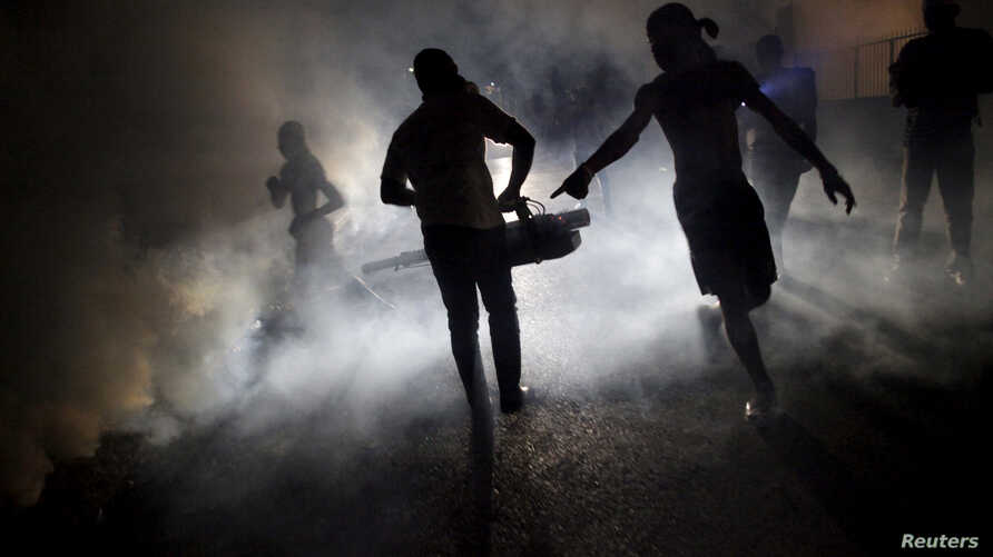 FILE - A worker of the Ministry of Public Health and Population fumigates in the street against mosquito breeding to prevent diseases such as malaria, dengue and Zika in Port-au-Prince, Haiti, on February 15, 2016.