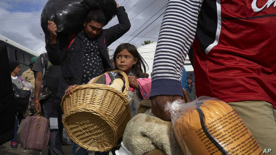 Brittany Rios, of Honduras, center, carries stuffed animals in a wicker basket as her family leaves a shelter for members of the Central American migrant caravan in Tijuana, Mexico, Nov. 30, 2018.