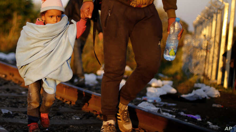 A father and his daughter cross the borderline on their way to a temporary holding center for migrants in the early morning at the border between Serbia and Hungary in Roszke, southern Hungary, Sept. 14, 2015.