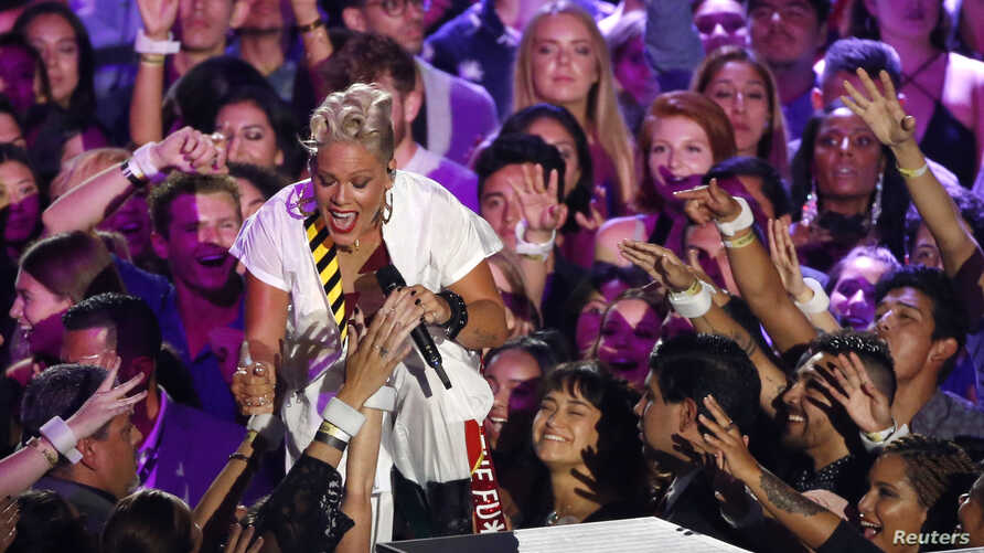 FILE - Singer Pink greets members of the audience as she performs during the 2017 MTV Video Music Awards show in Inglewood, California, Aug. 27, 2017.